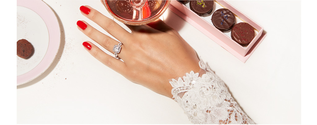 woman's hand with Kleinfeld ring next to wedding desserts