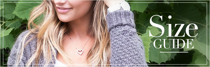 Necklace Length and Chain Length Size Guide. Close up image of a woman wearing a watch and a heart shaped diamond necklace standing in front of a wall of ivy.