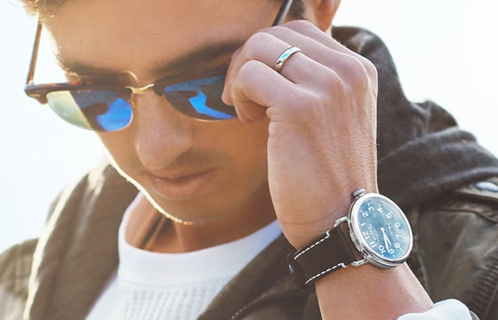 Image of a man wearing a watch with a brown strap and removing cool sunglasses.